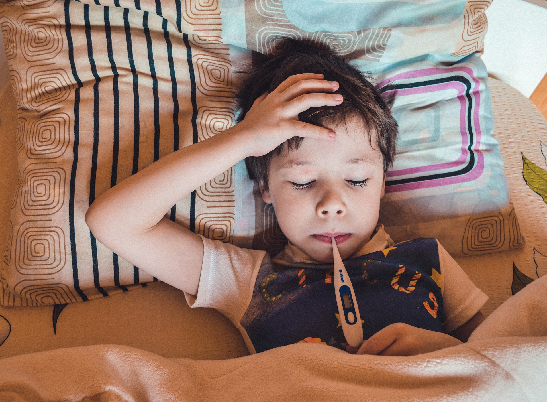 little boy sick with thermometer sick at Disneyland