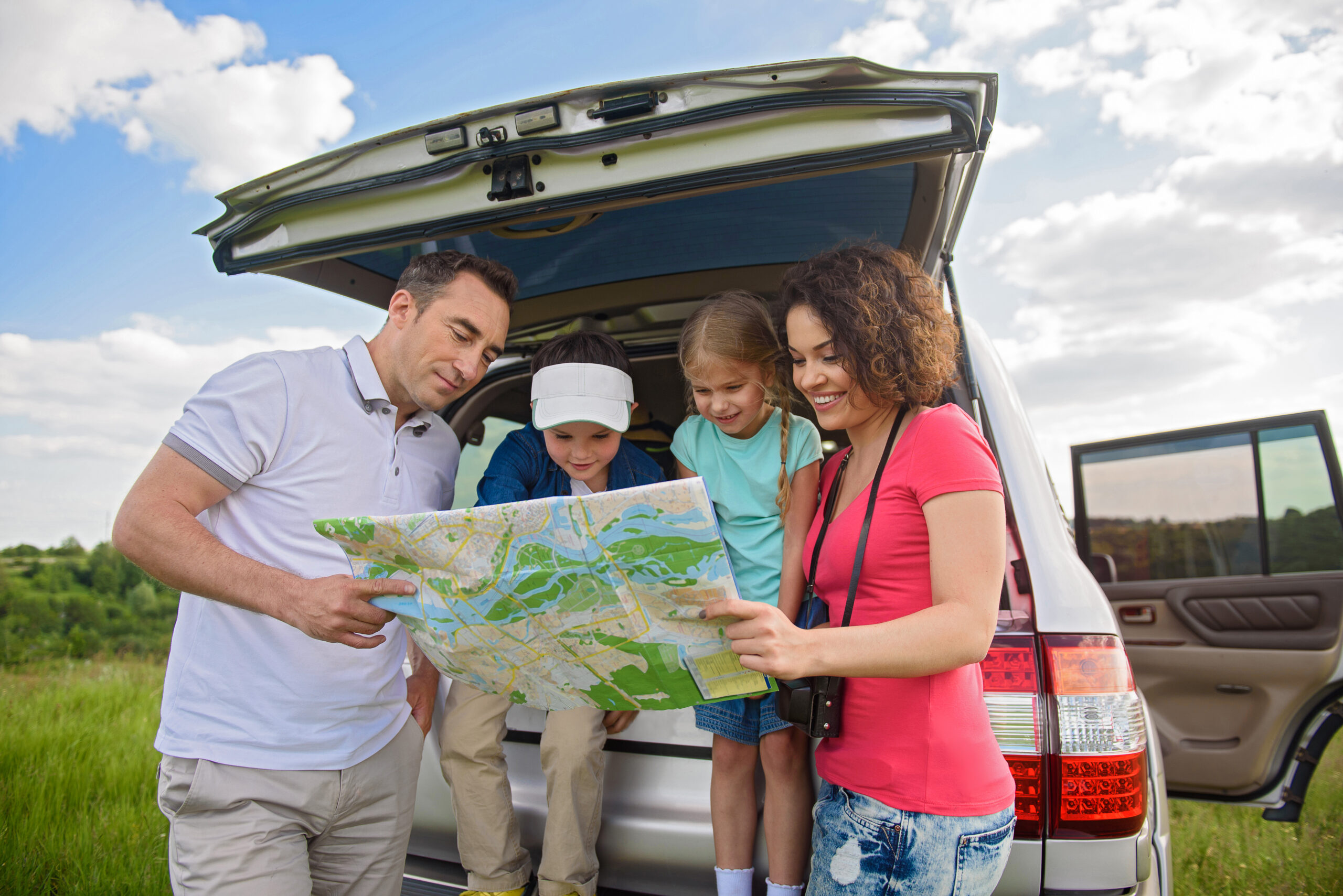 Family reading a map by car