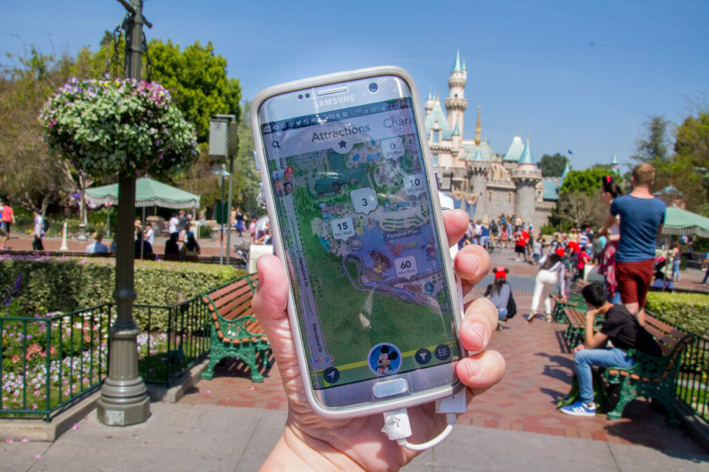 Phone with Disneyland App pulled up showing wait times, in a hand, with Disneyland castle in background
