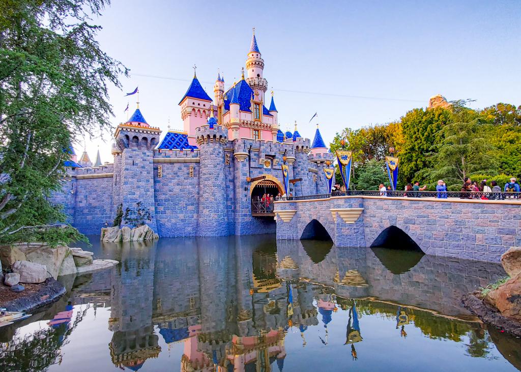 Sleeping Beauty Castle in Disneyland from the left side with Matterhorn peeking up over trees.